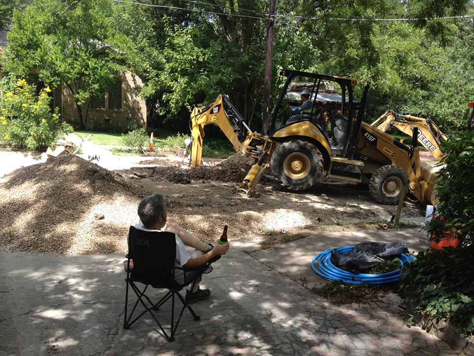 Frank enjoys a beer while he watches men dig a hole in our street